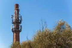 Antennes de télécommunication sur une vieille cheminée de brique Concept industriel Technologie moderne Lignes à haute tension en Photographie stock libre de droits