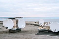 Antennes paraboliques, antennes de satellite sur le bâtiment dans la zone urbaine près de la rivière Image stock