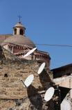 Antennes paraboliques satellites avec l'église Images stock