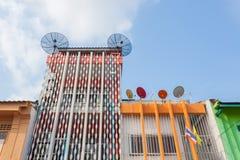 Antennes paraboliques sur la plate-forme de toit avec le bâtiment coloré sino-Portug Image libre de droits