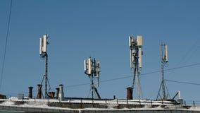 Antennes voor cellulair en mobiel communicatiemiddel over het dak Antennes van mobiele telefoonmededeling, televisie, Internet stock footage