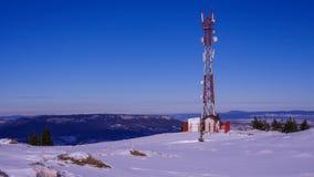 Antennrepetervapentorn överst av det snöig berget Royaltyfria Bilder