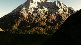 Antennskott över den gröna dalen till berget i snö på solnedgången royaltyfri illustrationer