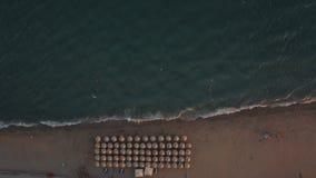 Antennskott av det blåa havet och sunbeds under paraplyer på stranden stock video