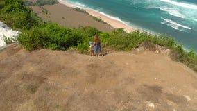 Antennskott av en ung kvinna och hennes son som besöker en avlägsen strand - nyangnyang- på den Bali ön Stå på en vagga stock video