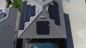 Antennskott av hus med paneler för sol- energi för eco på tak, liten suburbian sikt med sjön i 4k stock video
