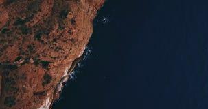 Antennskott av klippor som hänger över vatten i solnedgång arkivfilmer
