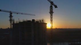 Antennskott av konstruktionsplatsen med kranar och arbetare på solnedgången arkivfilmer