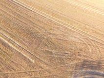 Antennskott av traktorspår i ett fält Arkivfoton
