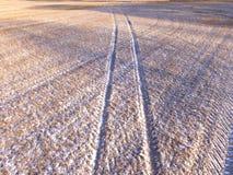 Antennskott av traktorspår i ett fält Arkivfoto