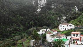 Antennskott Highland Village i en kanjon mellan två kullar och berg låg storm för oklarheter Palmträd och tätt arkivfilmer