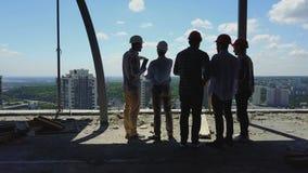 Antennskottet av byggmästare team på den bakre sikten för konstruktionsplatsen tillbaka av arbetaren som diskuterar plan av proje lager videofilmer