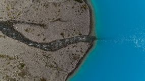 Antennskottet av den blåa is- sjön Blavatnet och floden tömmer in i det, Lyngen fjällängar royaltyfri bild