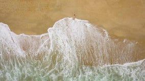 Antennskottet av en kvinna i en bikini som ligger på en sandig strand och vågor, tvättar hennes fot lager videofilmer