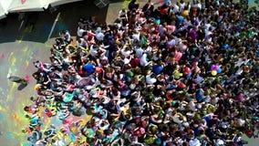 Antennskottet av hand och blåsa för lycklig flickatonåring en vinkande en kyss under Holi färgar festival med följande sikt av arkivfilmer