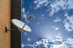 Anteny satelitarnej antena wspinał się na ścianie intymny dom na niebieskiego nieba tle zdjęcie royalty free