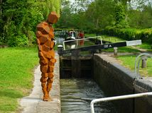 Anthony Gormley sculpture besides a canal lock Stock Photo