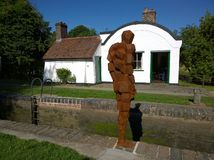 Anthony Gormley sculpture and lock keepers house Royalty Free Stock Photo