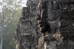 Anthropomorphic faces carved into stone at the Bayon Wat, a 12th century temple within the Angkor Thom comp stock image