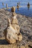 Anthropomorphic skulpturmades vid lantliga stenar på stranden royaltyfria foton