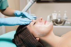 Anti--åldras ansikts- massage cosmetologist som gör massagen för ung kvinna på den Spa salongen fotografering för bildbyråer