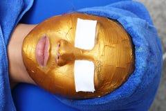 Anti-åldras ansiktsbehandling med guld- maskeringskrämmassage royaltyfri fotografi