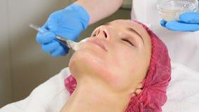 Anti-åldras ansiktsbehandling med maskeringskrämmassage på kvinnaframsida Genomskinlig flytande med collagenen, skönhetvitami lager videofilmer