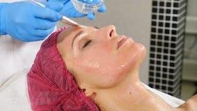Anti-åldras ansiktsbehandling med maskeringskrämmassage på kvinnaframsida Genomskinlig flytande med collagenen, skönhetvitami stock video