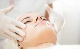Anti ageing facial massage. Beautiful young girl receiving anti ageing facial massage at cosmetics stock images