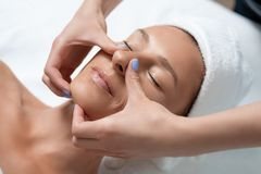 Attractive middle aged lady receiving face massage at spa salon royalty free stock photo