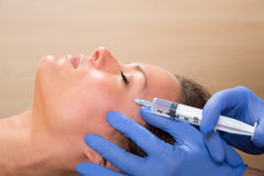 Anti aging facial mesotherapy syringe on woman face. Anti aging facial mesotherapy with syringe closeup  on woman face Royalty Free Stock Photo