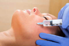 Anti aging facial mesotherapy syringe on woman face. Anti aging facial mesotherapy with syringe closeup  on woman face Royalty Free Stock Photography