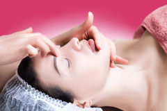 Anti-aging massage, anti-wrinkle treatment, facial skin care. Beautiful and well-groomed girl doing facial massage, Wrinkle control, close-up portrait, smooth Royalty Free Stock Photography