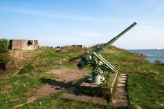 Anti-aircraft gun. In the background of blue sea in Scandinavia Royalty Free Stock Image
