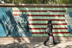 Anti american propaganda mural on tehran street iran. Veiled muslim woman walking by anti american and israel propaganda mural on tehran street iran outside stock images