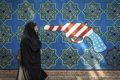 Anti american propaganda mural on tehran street iran. Veiled muslim woman walking by anti american and israel propaganda mural on tehran street iran outside royalty free stock image