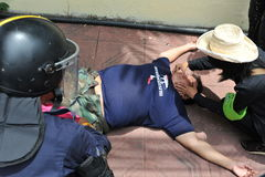 Anti-Amnesty Bill Rally in Bangkok. A protester receives medical attention after collapsing during scuffles with anti-government protesters and riot police near Stock Images