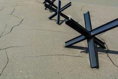 Anti--behållare damm från stänger på sprucken gammal asfalt mot våld kriga royaltyfri bild