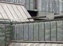 Anti beklim veiligheidsrollen met aren met weerhaken op de muren en het dak van een hoog veiligheidsgebouw met grijze het hellen  stock foto