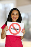 Anti Bullying. Teen girl holding a card that says no bullying royalty free stock photography