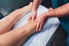 Anti--cellulite massage p? benen av unga kvinnor royaltyfria bilder