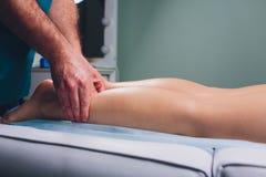 Anti--cellulite massage p? benen av unga kvinnor royaltyfri fotografi