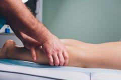 Anti--cellulite massage p? benen av unga kvinnor arkivbild