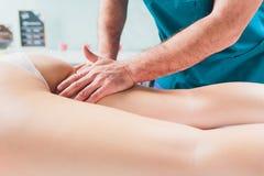 Anti--cellulite massage p? benen av unga kvinnor arkivfoto