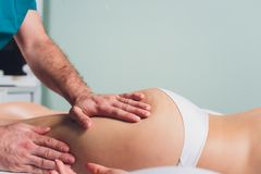 Anti--cellulite massage p? benen av unga kvinnor royaltyfria foton