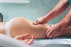 Anti--cellulite massage p? benen av unga kvinnor royaltyfri foto