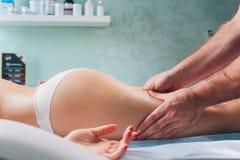Anti--cellulite massage p? benen av unga kvinnor royaltyfri bild