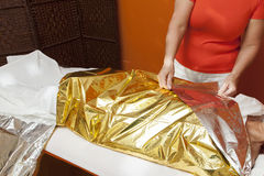 Anti cellulite treatment, body wrapping. Mid aged female body being wrapped around with foil to reduce fat, special anti cellulite treatment, series of HQ photos Royalty Free Stock Photography