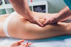 Anti-Cellulitemassage auf den Beinen von jungen Frauen lizenzfreie stockbilder