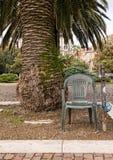 Anti-diefstal apparaat - de stoel padlocked aan post onder palm Stock Afbeeldingen